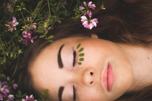 woman lying in flowers with eyes closed