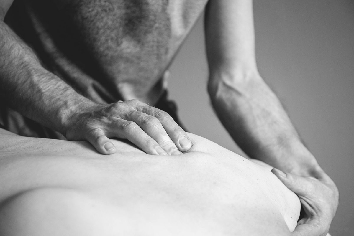 practitioner performing back massage