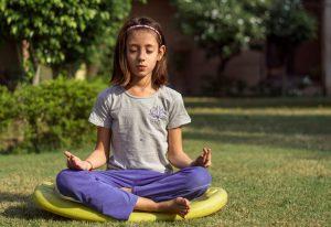 girl sits in garden crossed legged, meditating