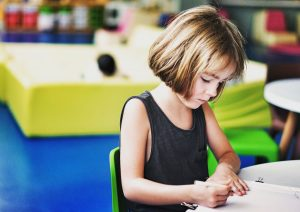 young girl writing on desk - neuro-development
