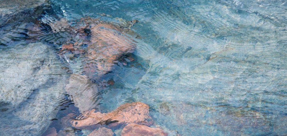 glimpses of rocks through blue sea