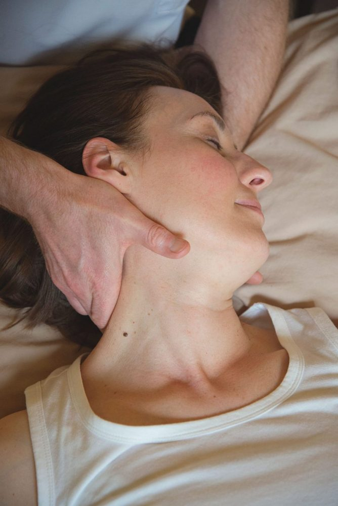 woman having osteopathy treatment on back of head and neck